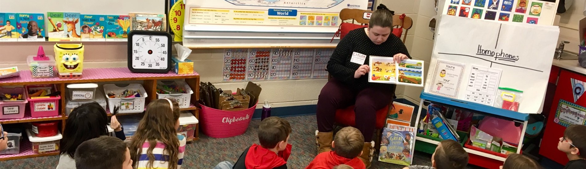 Volunteer reading to a class of students.